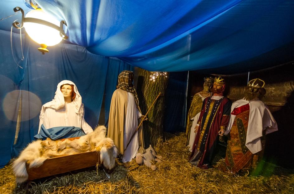 På katolska kyrkans innergård sitter Maria nyförlöst men fräsch och med perfekt ögonmejk - de tre visa männen ser dock slitna ut